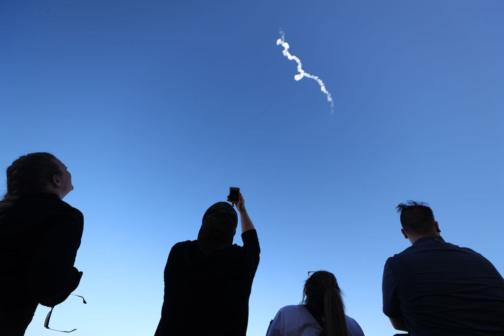 People looking up from Earth at New Shepard which launched into the sky