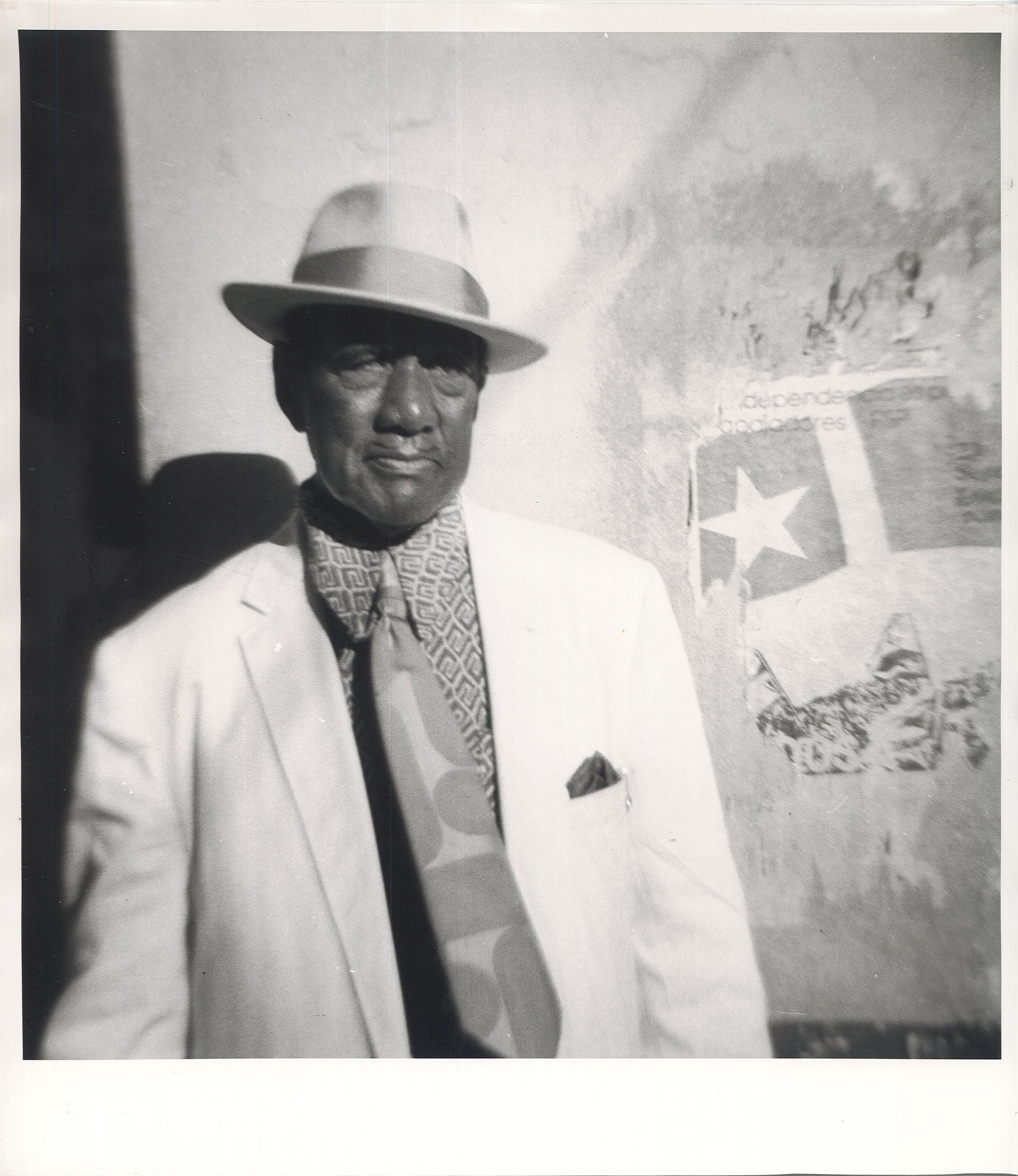 An older man in a fedora, suit and tie