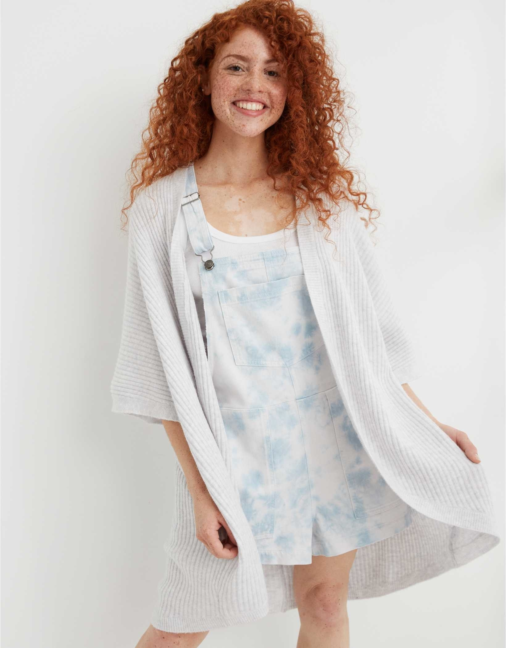 A model wearing the white sweater wrap over a pari of overalls
