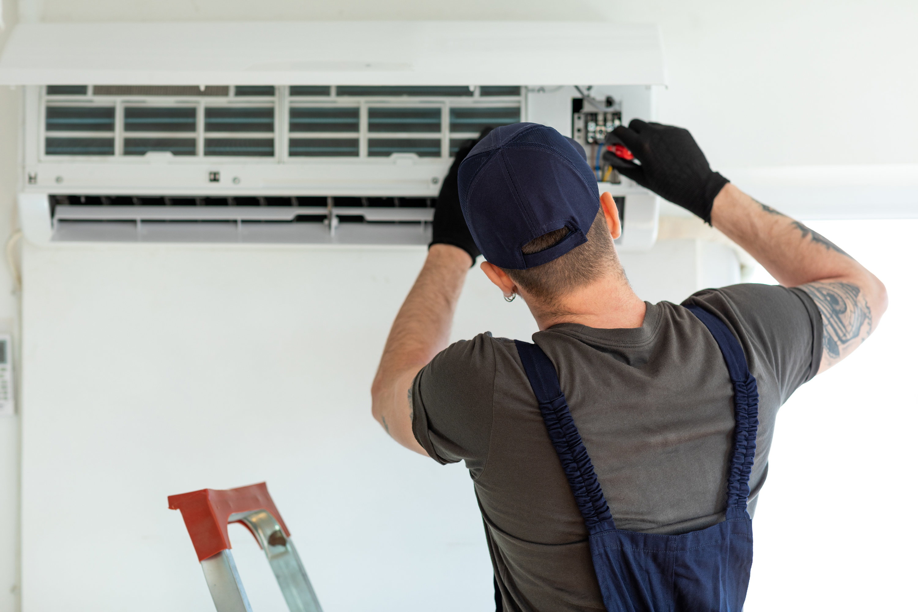 A maintenance worker fixing an air conditioning unit