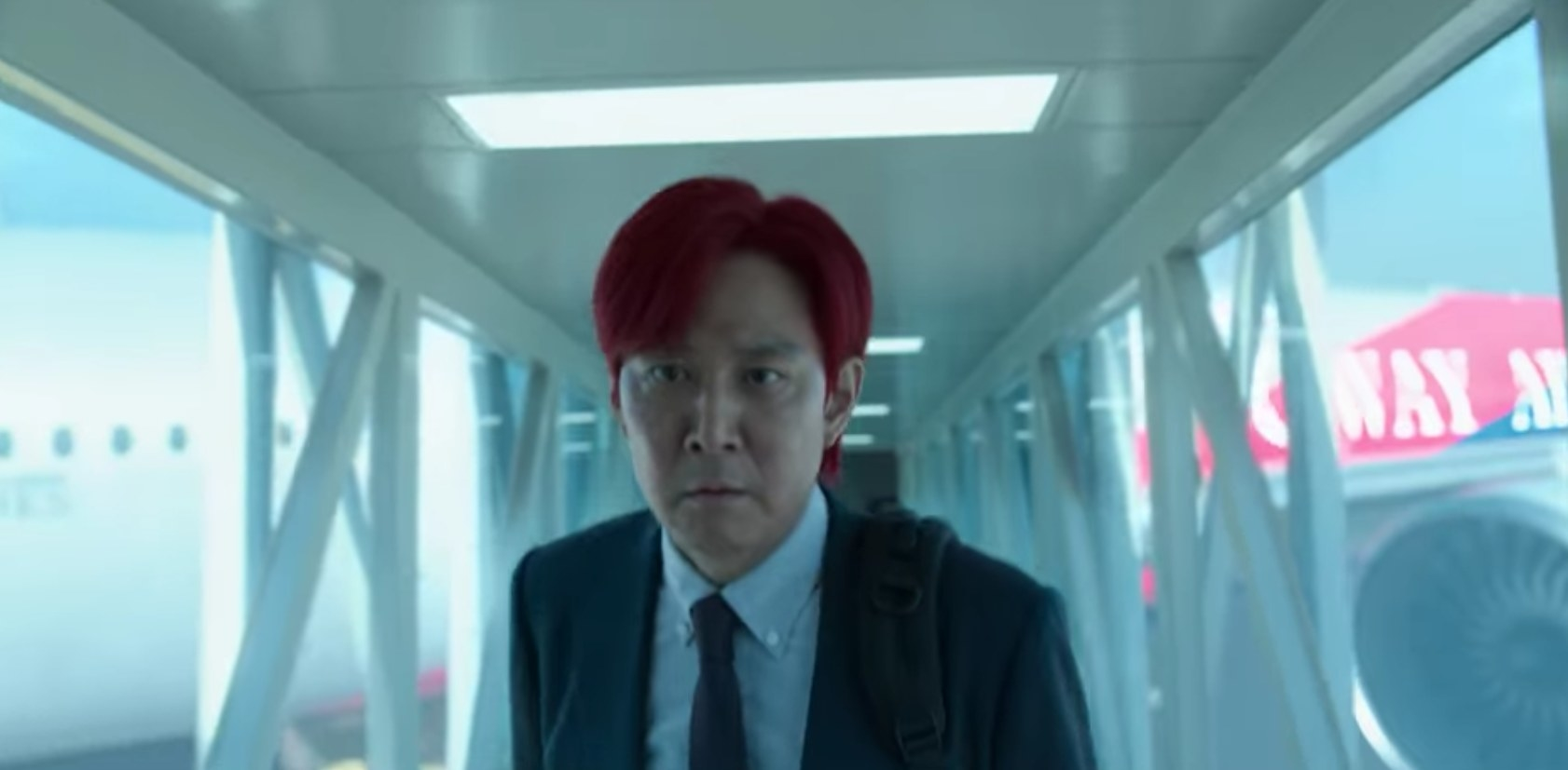 A red-haired Gi-hun looks determined while walking up a tunnel away from an airplane