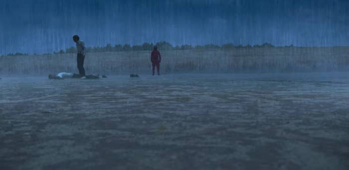 Gi-hun stands over Sang-woo, who lies on the ground in the rain; a guard watches on