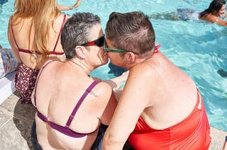 Two older women with short hair in swimsuits kissing by the edge of a pool