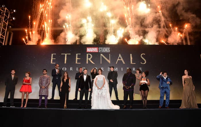Cast members in front of an Eternals world premiere banner and fireworks