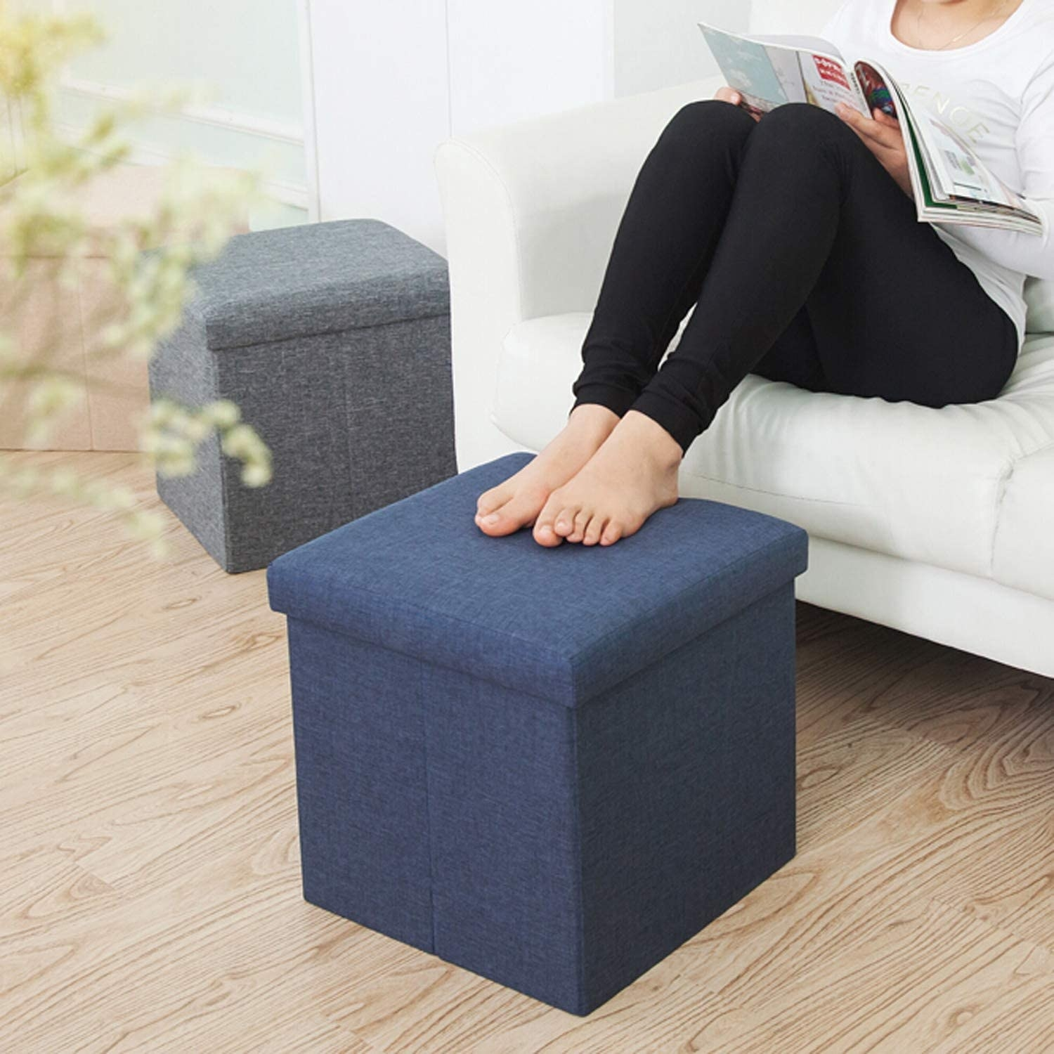 Person with feet up on a navy blue linen ottoman