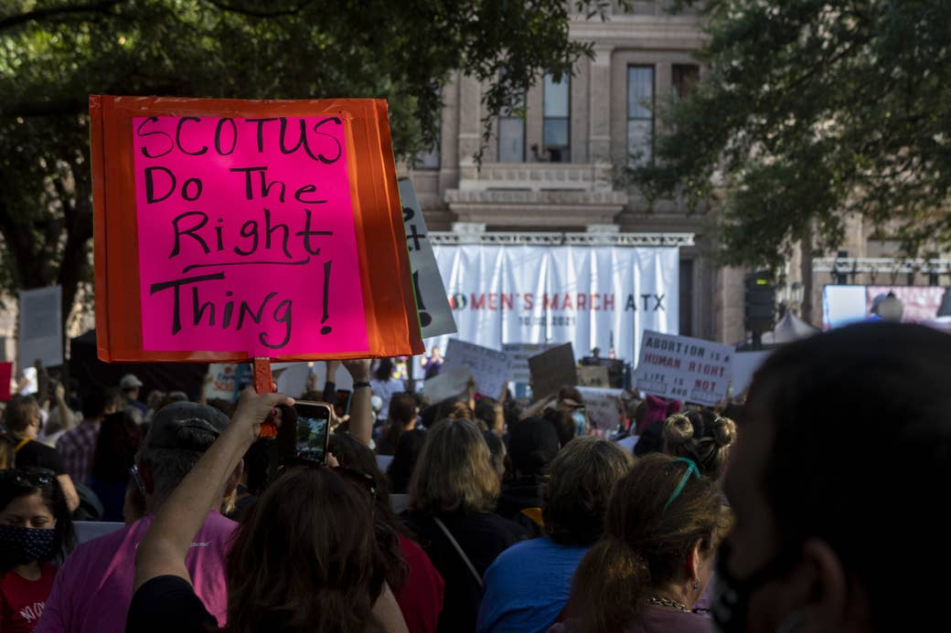 """People in a crowd hold up signs, including """"SCOTUS Do the Right Thing!"""""""