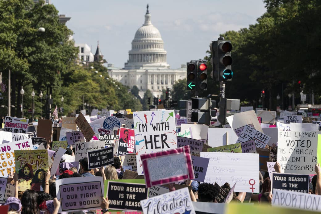 """Protesters holding up many signs, such as """"Our Future Our Fight Our Bodies,"""" with the US Capitol in the background"""