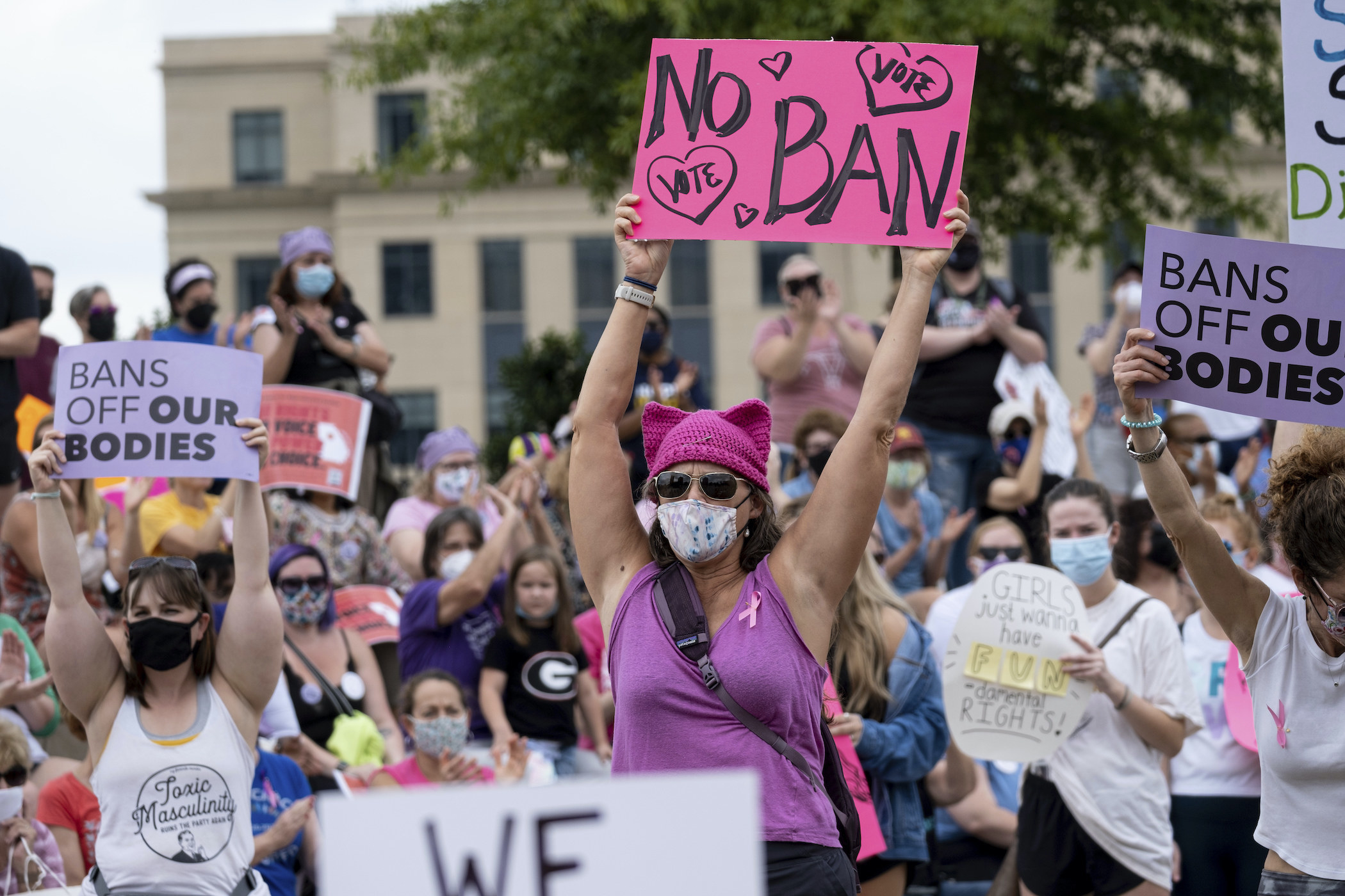 """Protesters wearing masks and some holding signs, including """"Bans Off Our Bodies"""""""