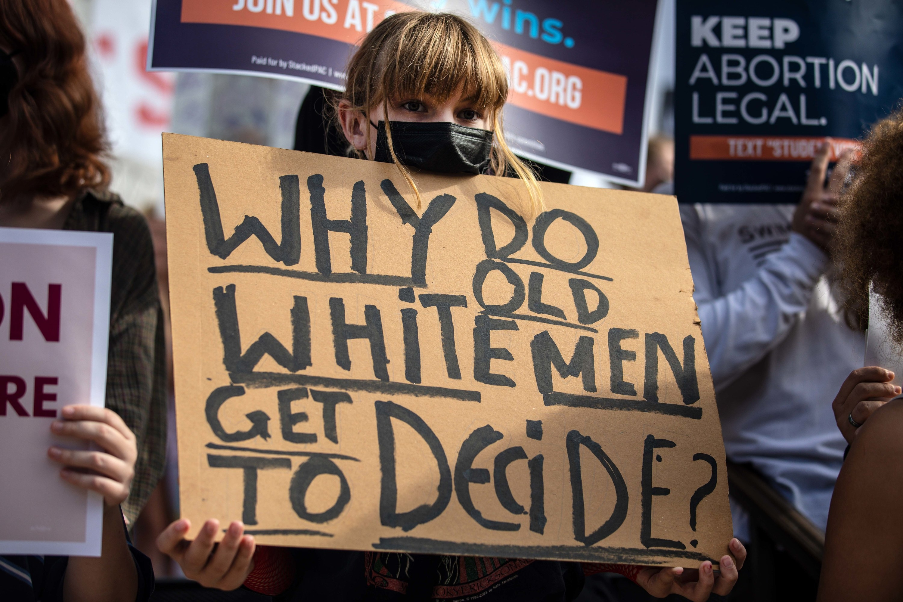 """A person holds a sign that reads """"Why Do Old White Men Get to Decide?"""""""