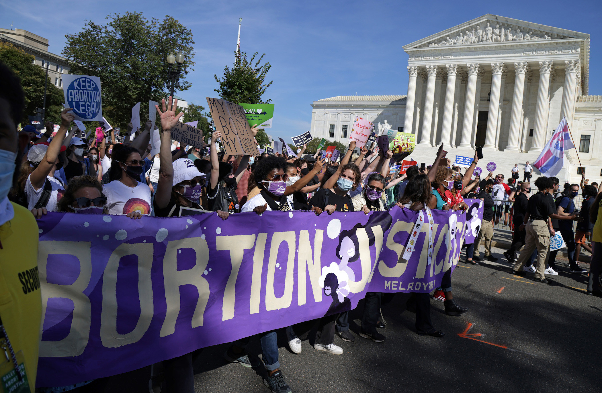 """Protesters carry a banner saying """"Abortion Justice"""""""