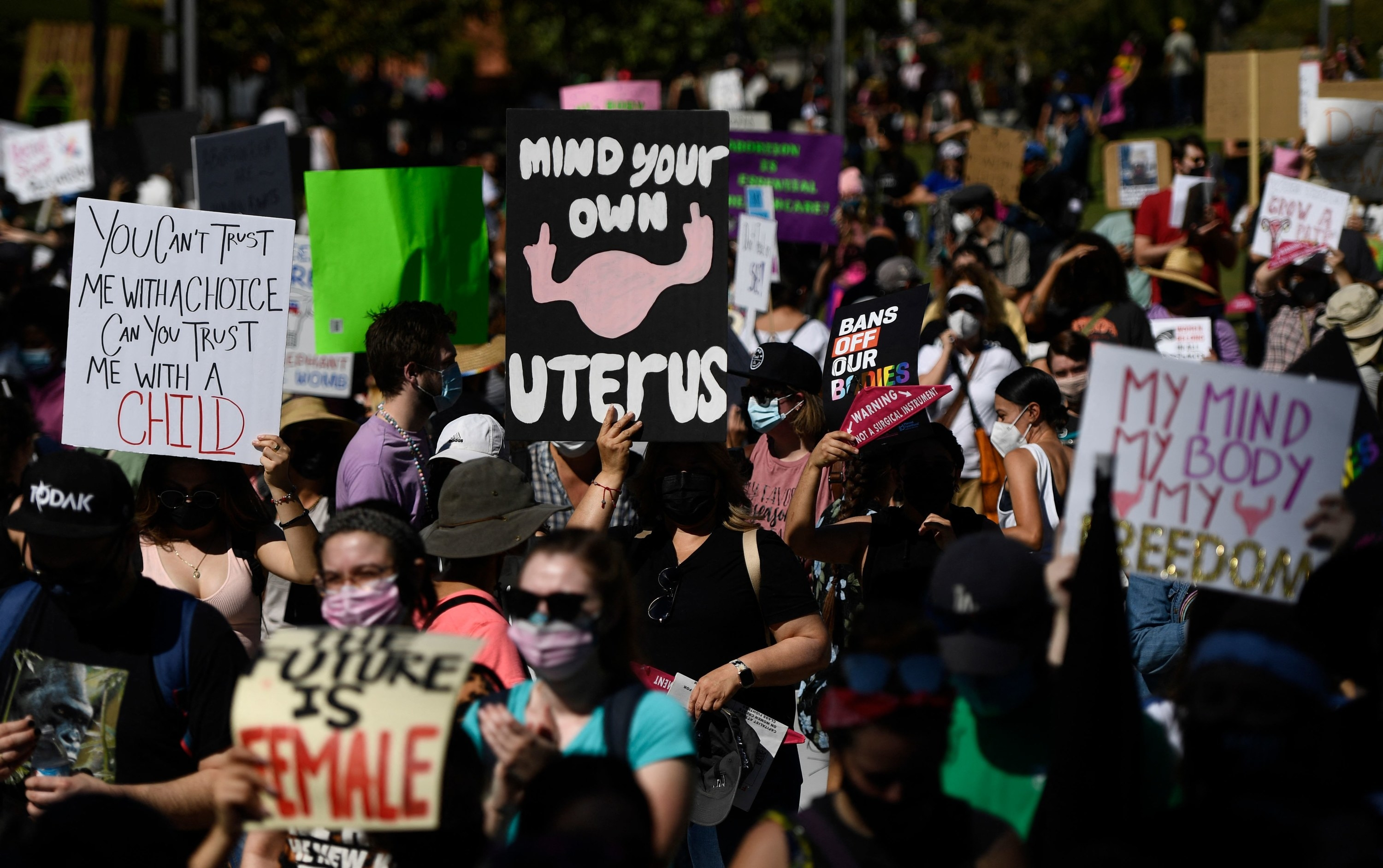 """Masked protesters carry signs, including """"Mind Your Own Uterus"""" and """"The Future Is Female"""""""