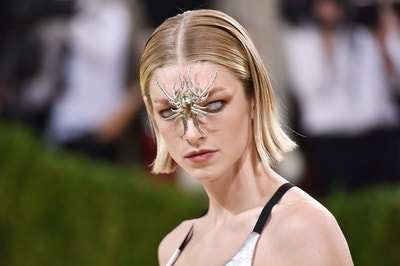 Hunter Schafer wearing whiteout contacts and a spider charm in between her eyes
