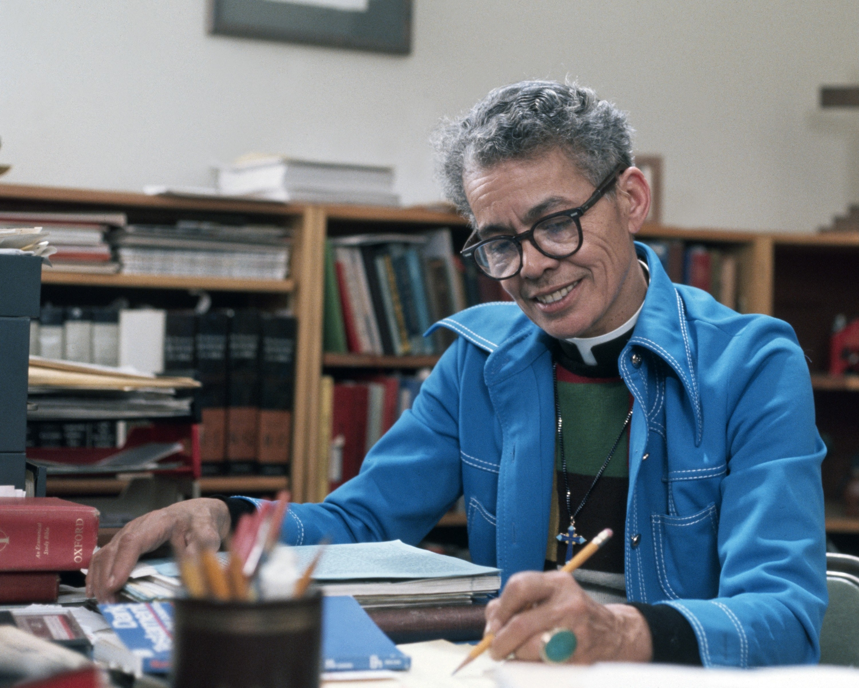 Pauli Murray sits at a desk writing