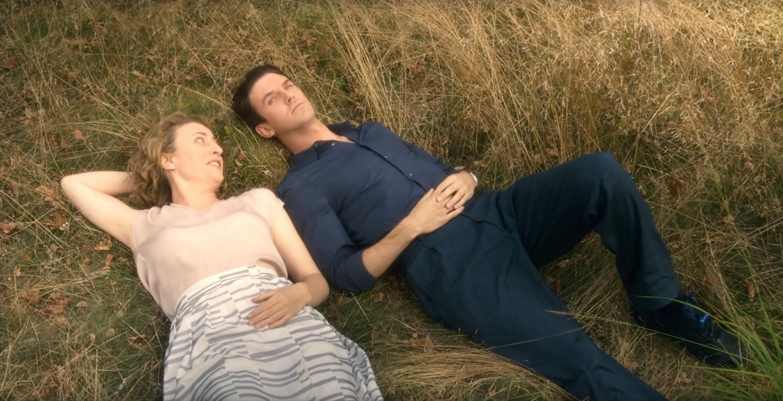 Maren Eggert and Dan Stevens lay in a grass field
