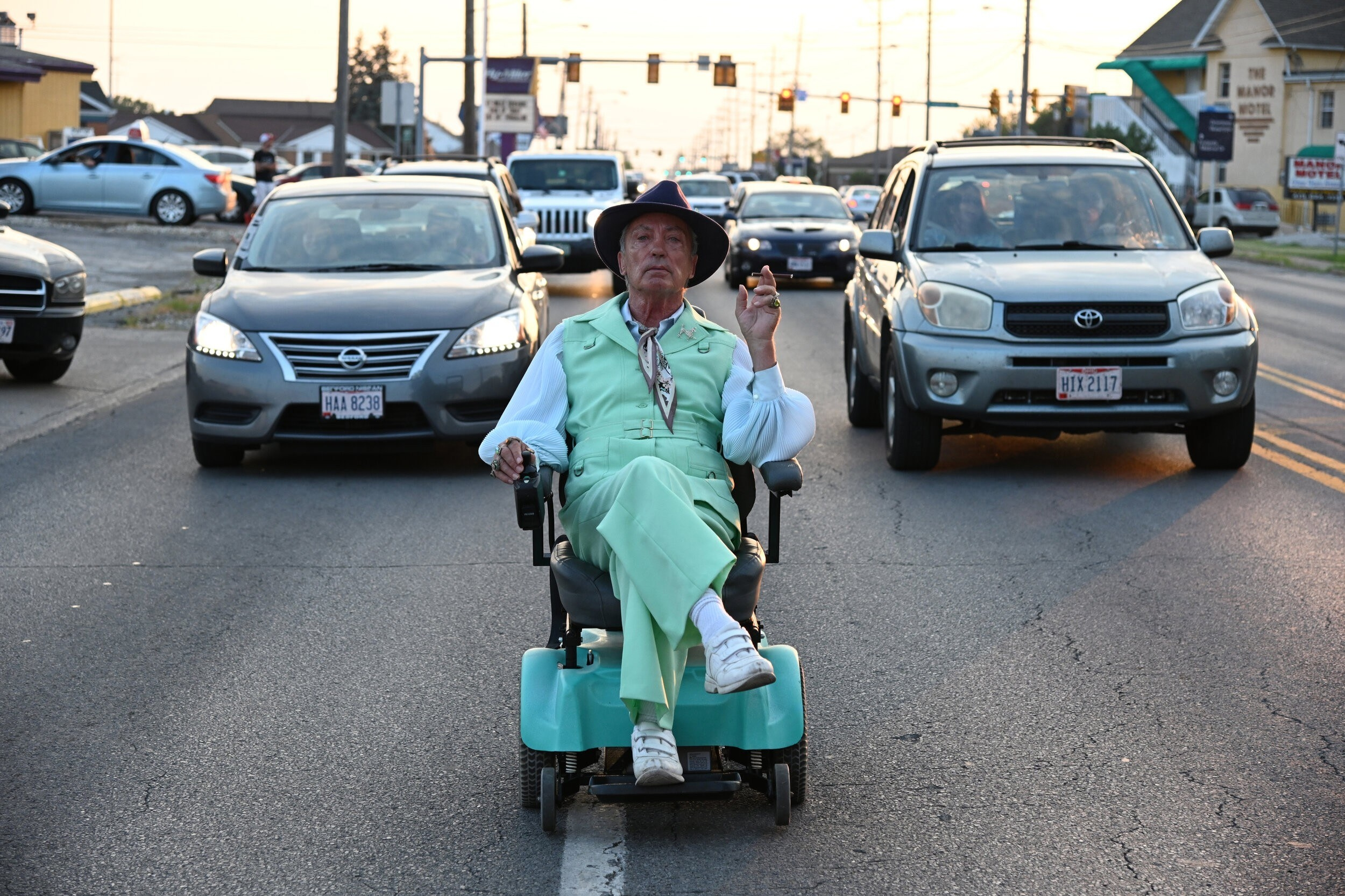 Udo Kier sits in a motorized chair in the middle of the road