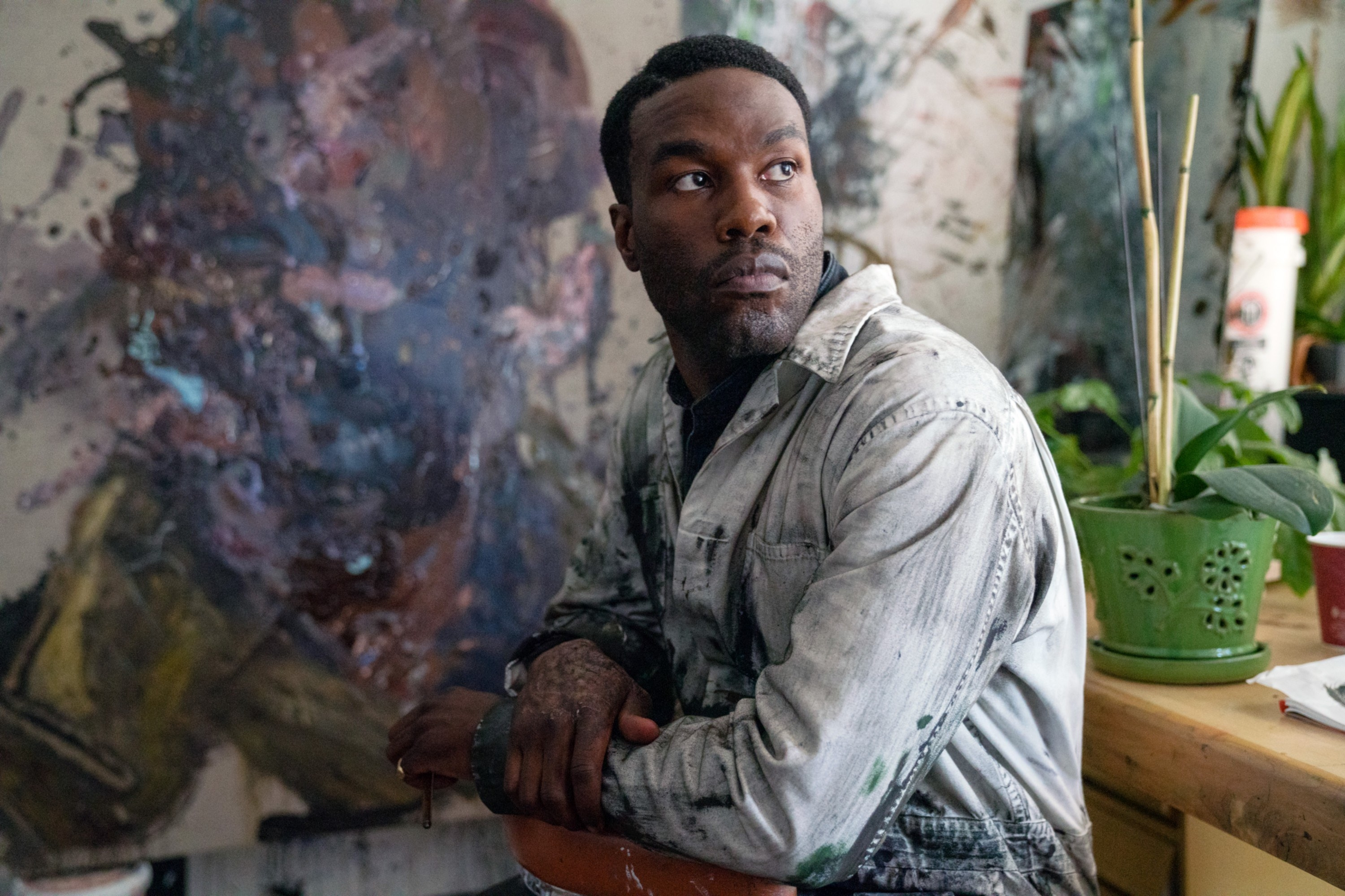 Yahya Abdul-Mateen II sitting beside a painting in coveralls