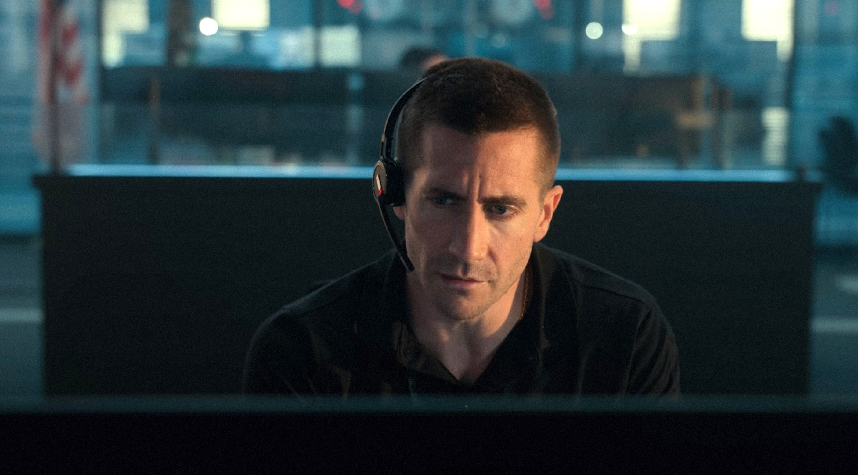 Jake Gyllenhaal sits in a call center with a headset on