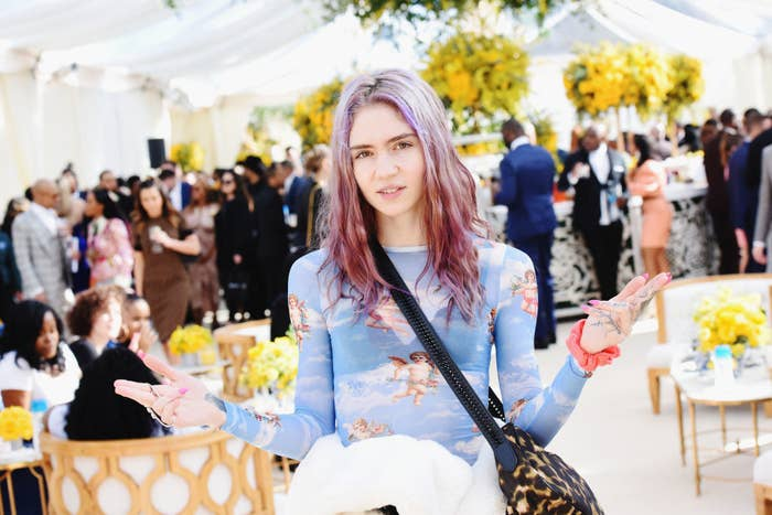 Grimes at an event, standing with a shoulder bag and arms outstretched
