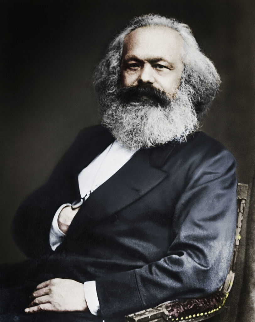 Karl Marx with a major beard sitting in a chair