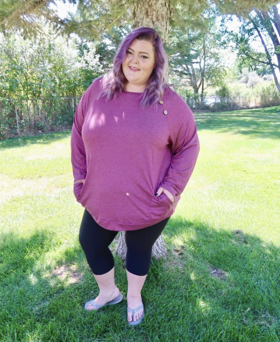 a reviewer wearing the shirt in the wine red color with black leggings
