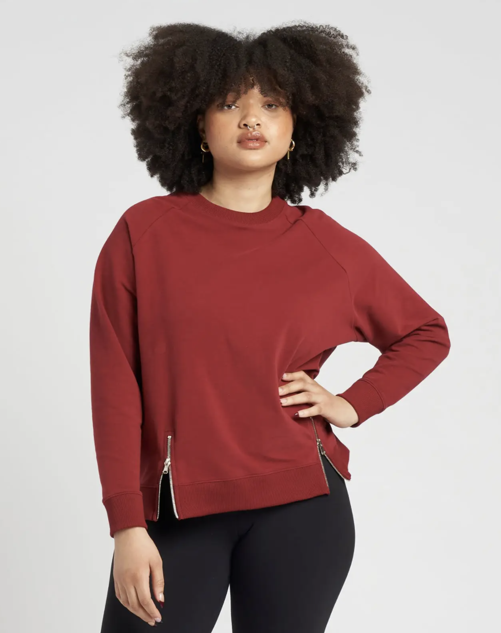 model wearing red pullover with black leggings