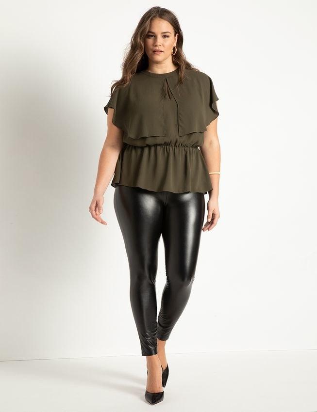 model wearing olive peplum top with black shiny leggings