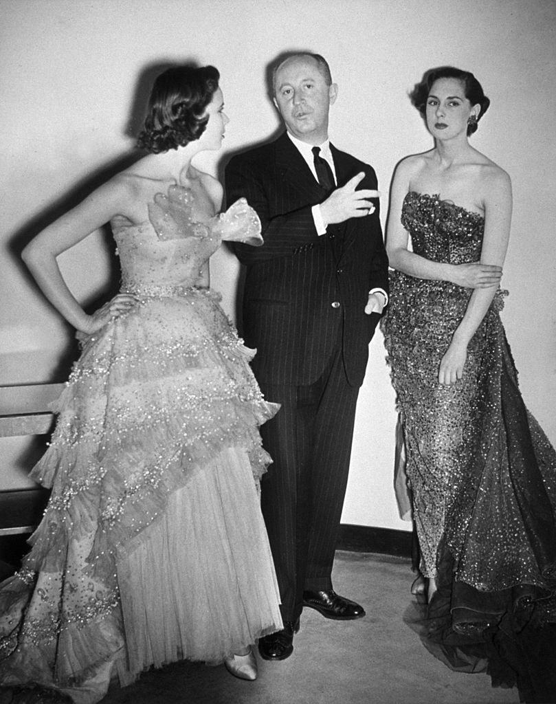 Pictured is Christian Dior with two models wearing his designs.