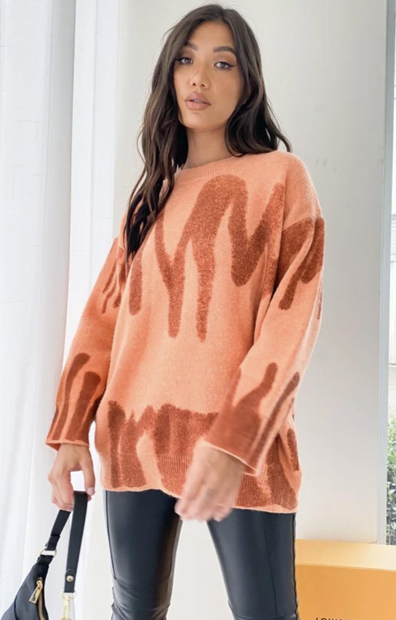 model wearing orange sweater with black shiny leggings
