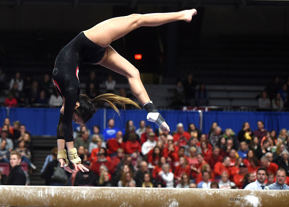 Gymnast doing a flip on a bar