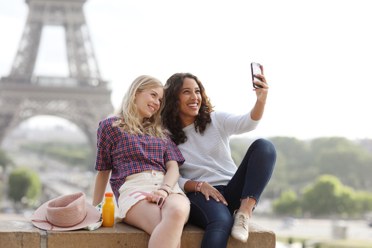 Two friends taking a selfie in front of the Eiffel Tower