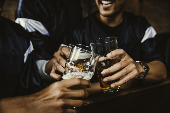A bunch of guy friends drinking at a bar together