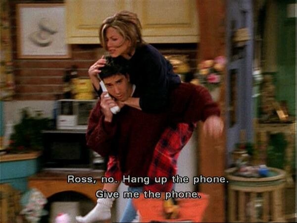 Ross listening to a message from Rachel as she jumps on his back and tries to stop him