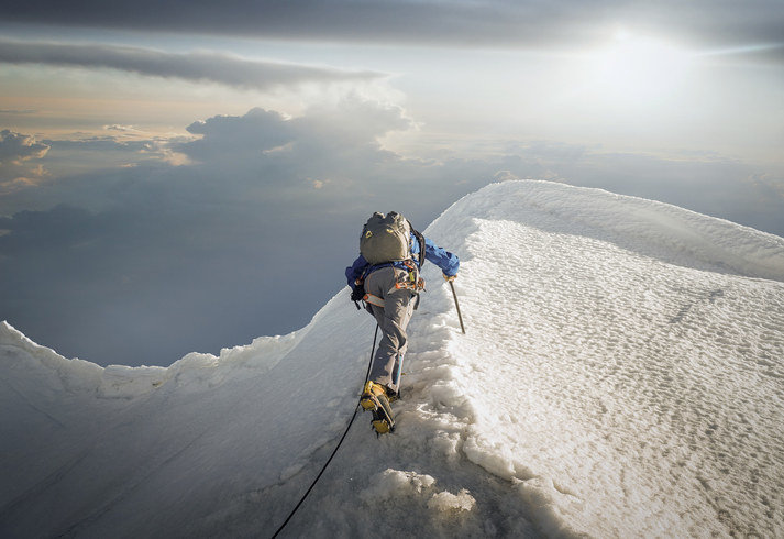 Mountain climber at the top of snowy mountains