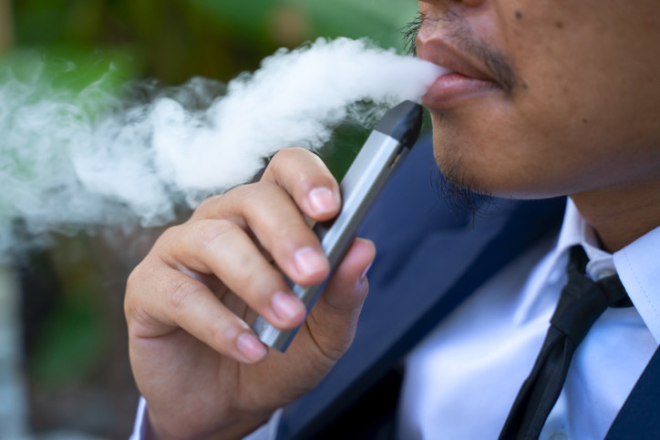 A business man smoking a vape