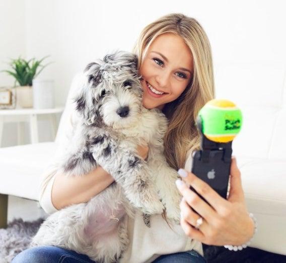 Model with dog holding pooch selfie stick.