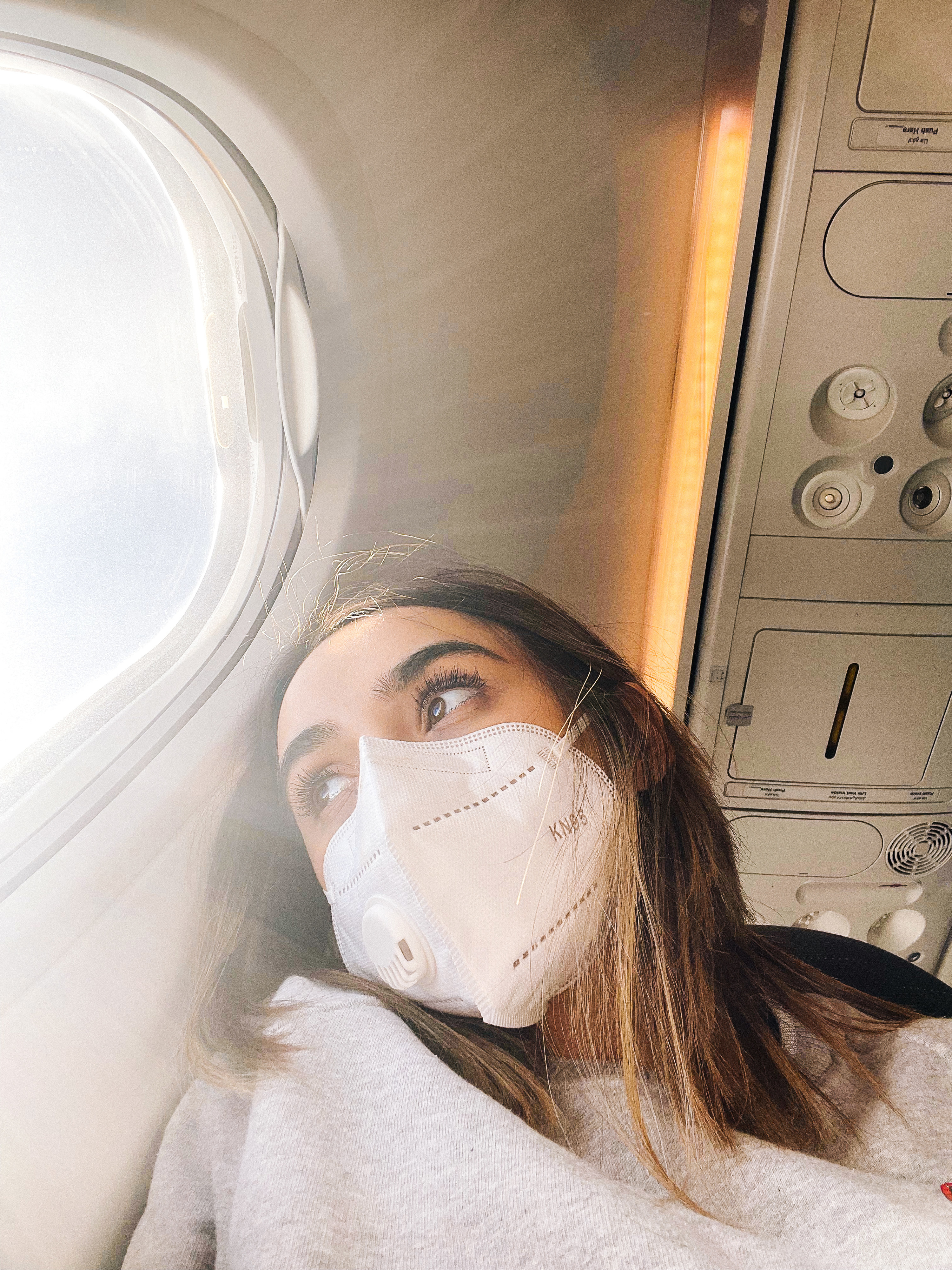 A woman looking out a plane window with mask on