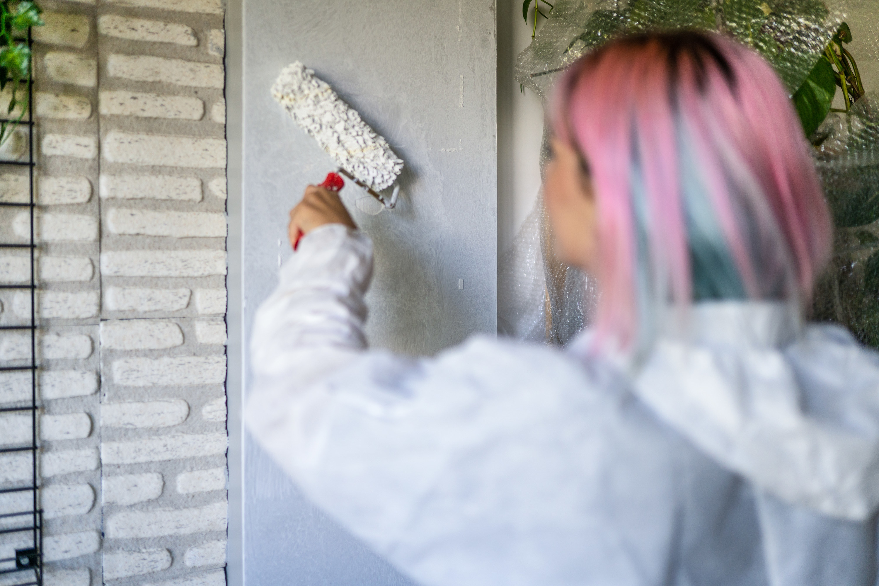 A woman with colorful hair painting a wall with a roller