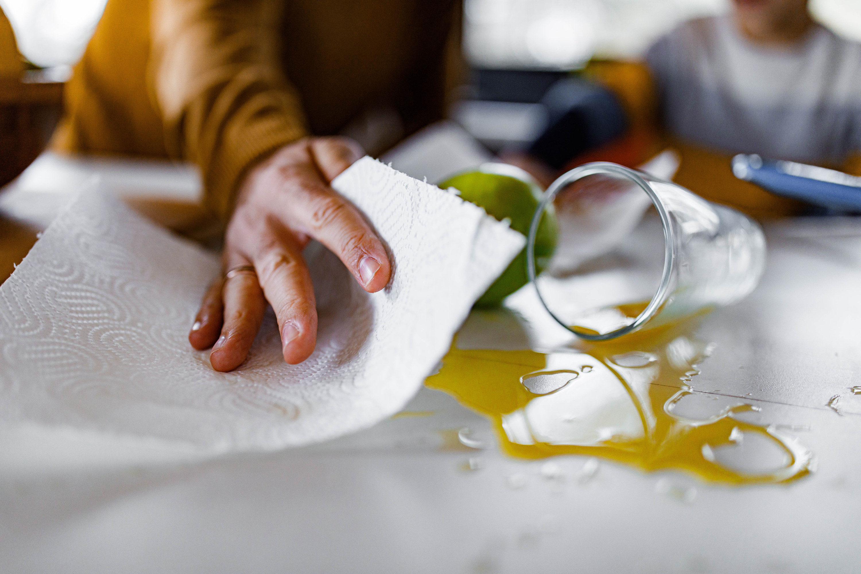 Closeup of a hand cleaning up spilled juice with a paper towel