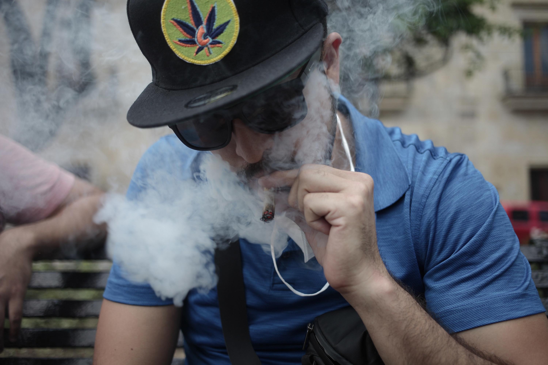 A guy smoking a joint wearing a marijuana hat and dark sunglasses