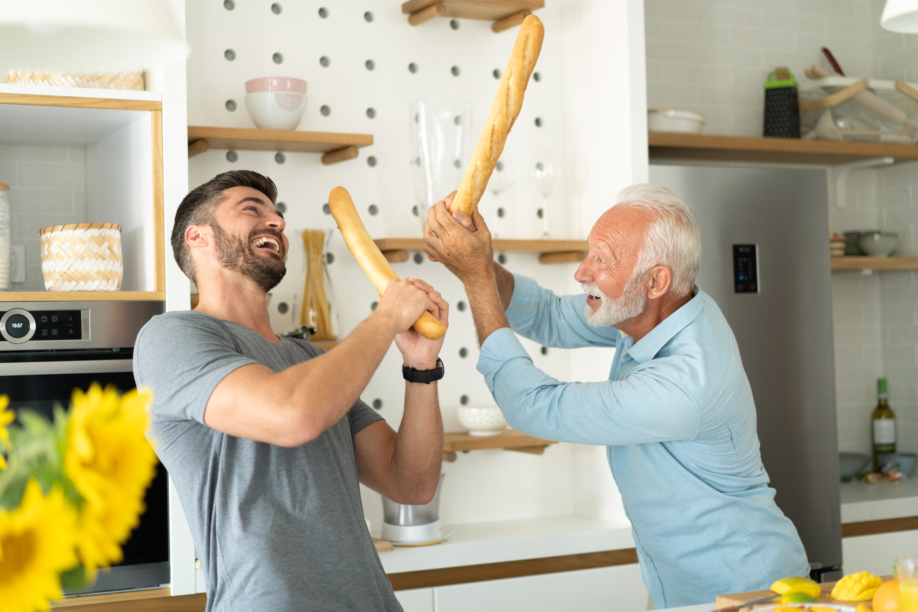 A man and his senior father play fighting with baguettes in a kitchen