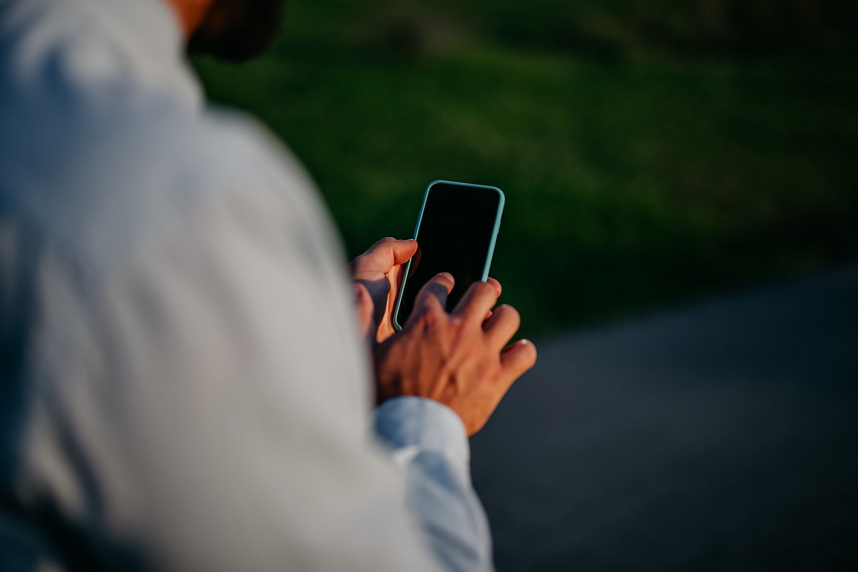 Back view of a man holding a blank iPhone and tapping it