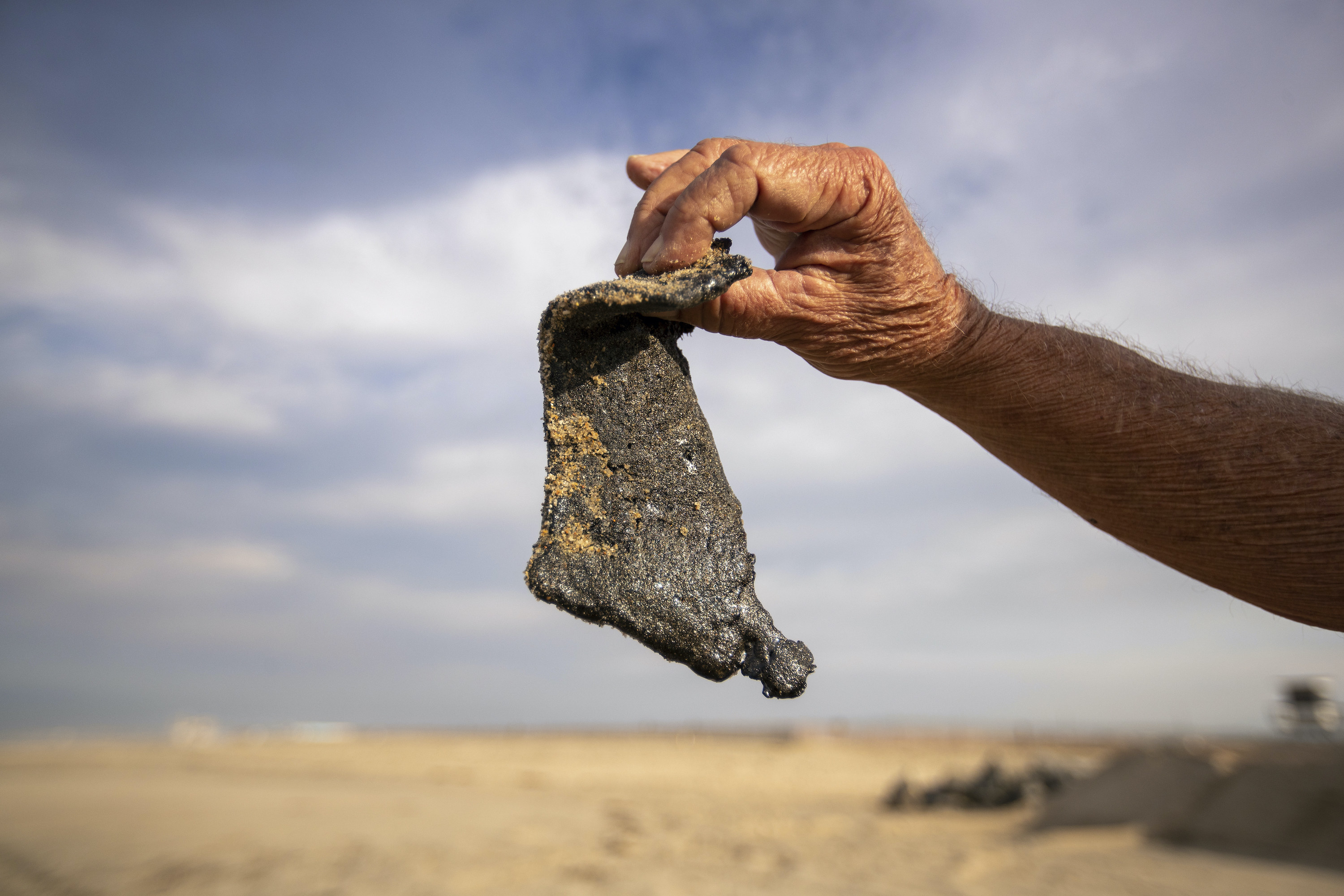 A man holds an oil globule larger than his hand that was found on the beach