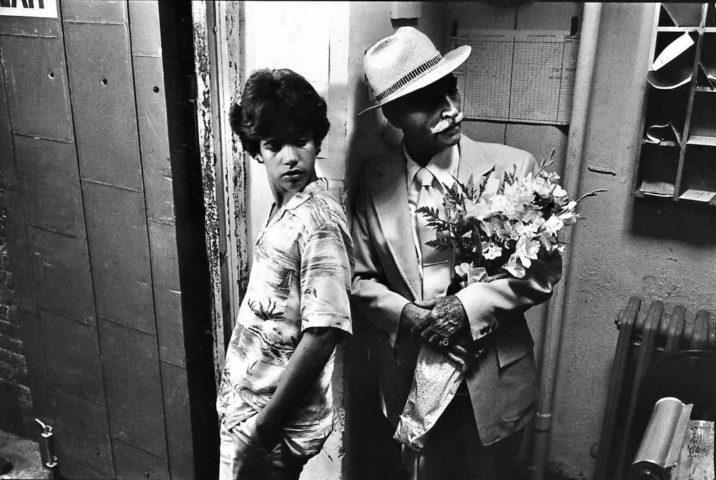 A young man and an old man with flowers lean on a post at the entrance to an apartment building