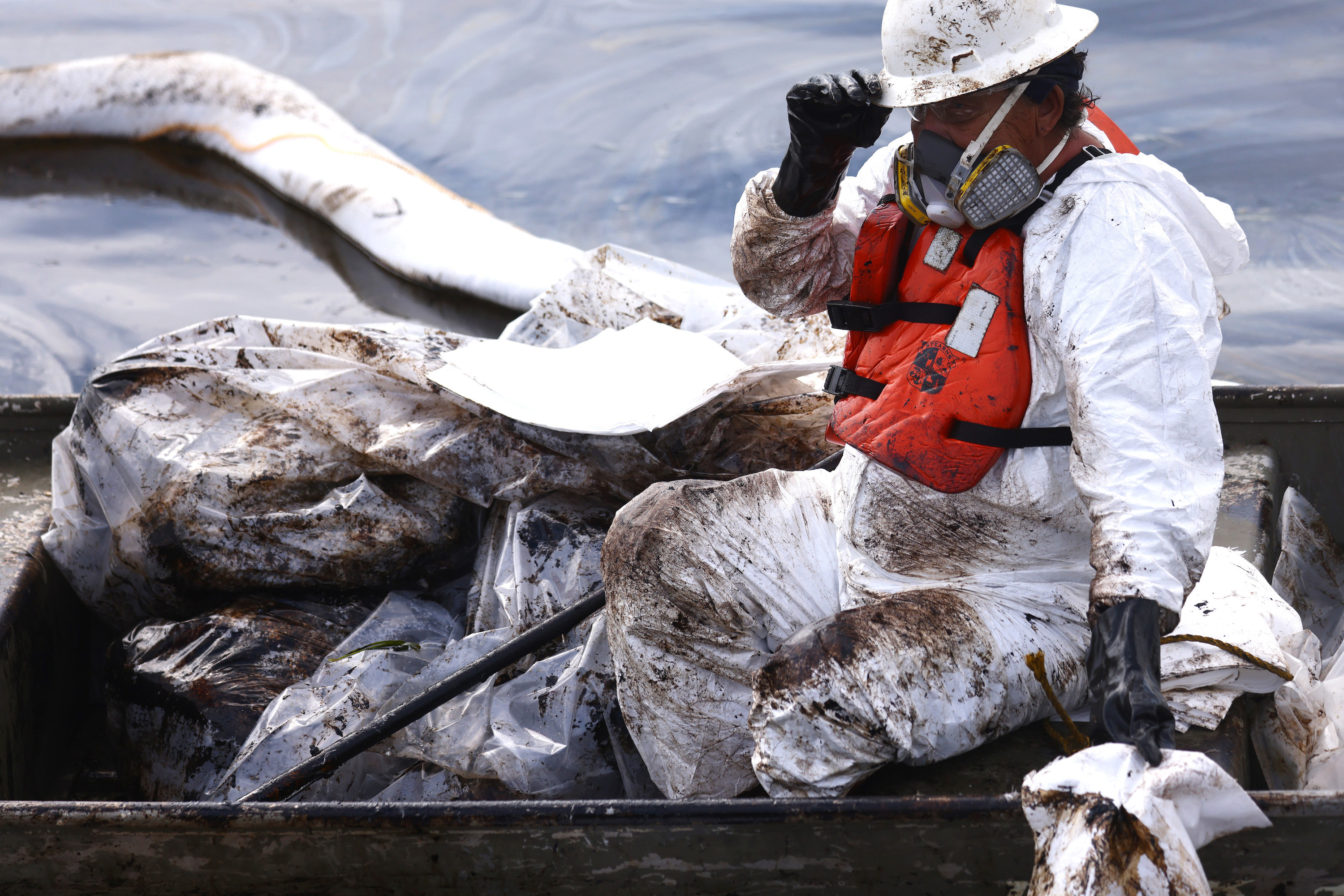 A cleanup worker wears a life vest and coveralls covered with dark residue from the oil spill