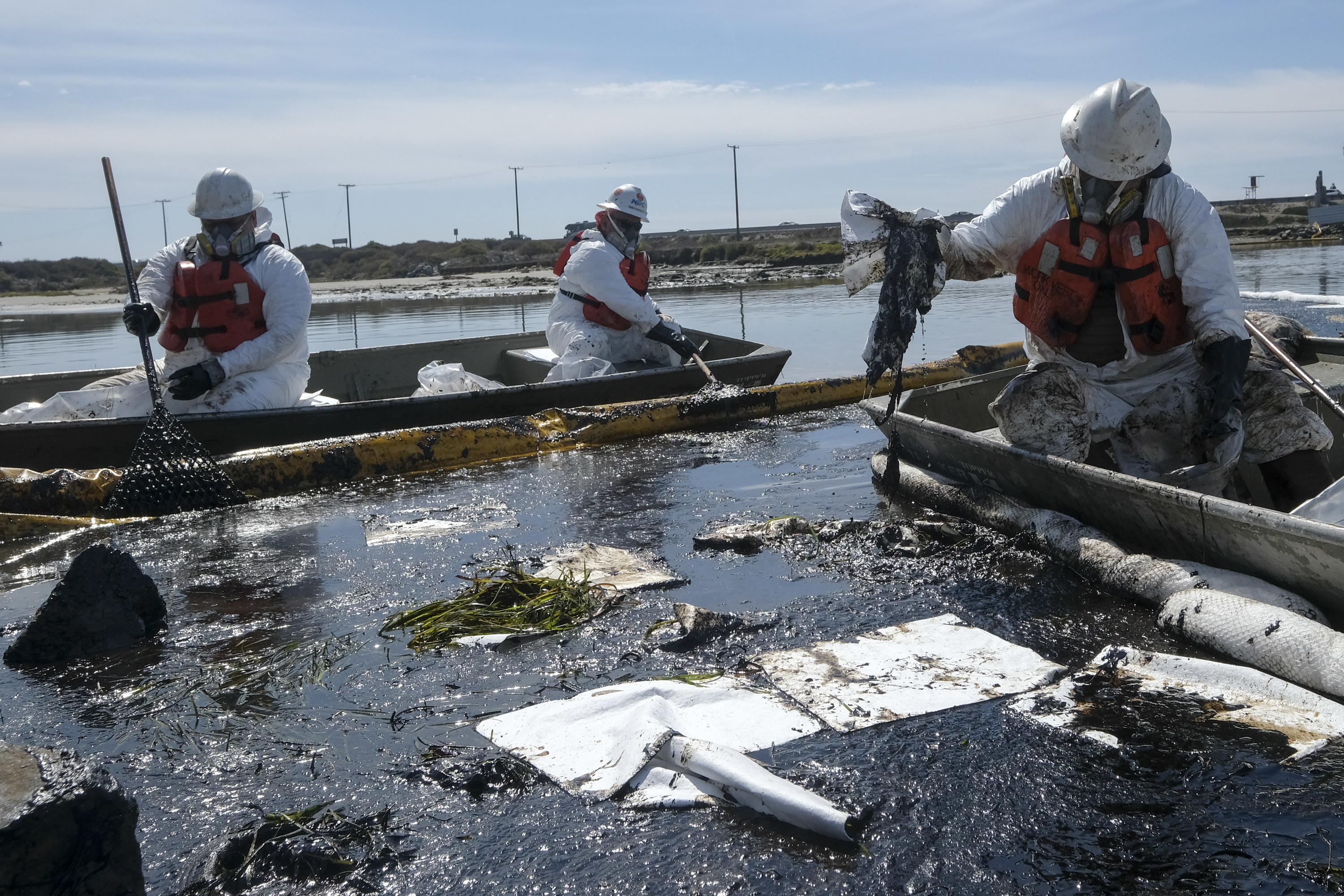 Workers in skiffs navigate oil-filled waters and attempt to clean up the mess from the oil spill