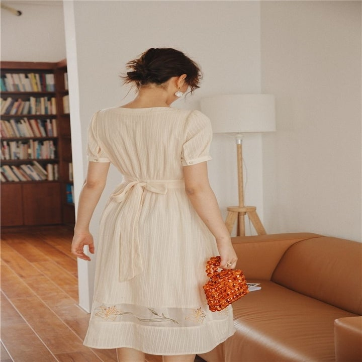 the back of the midi dress with a sheer panel at bottom and a tie