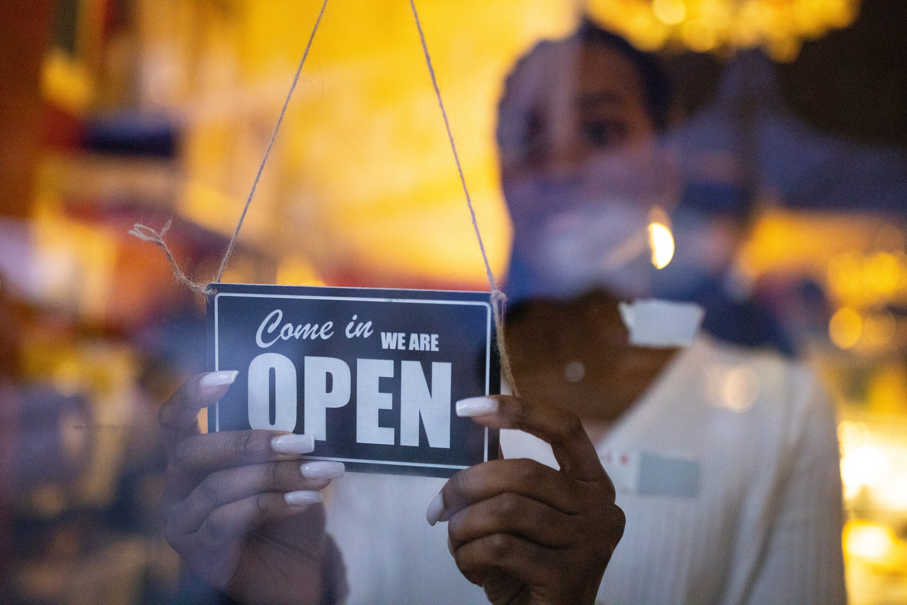 """Person changing a restaurant's open/close sign to """"come in, we are open"""""""