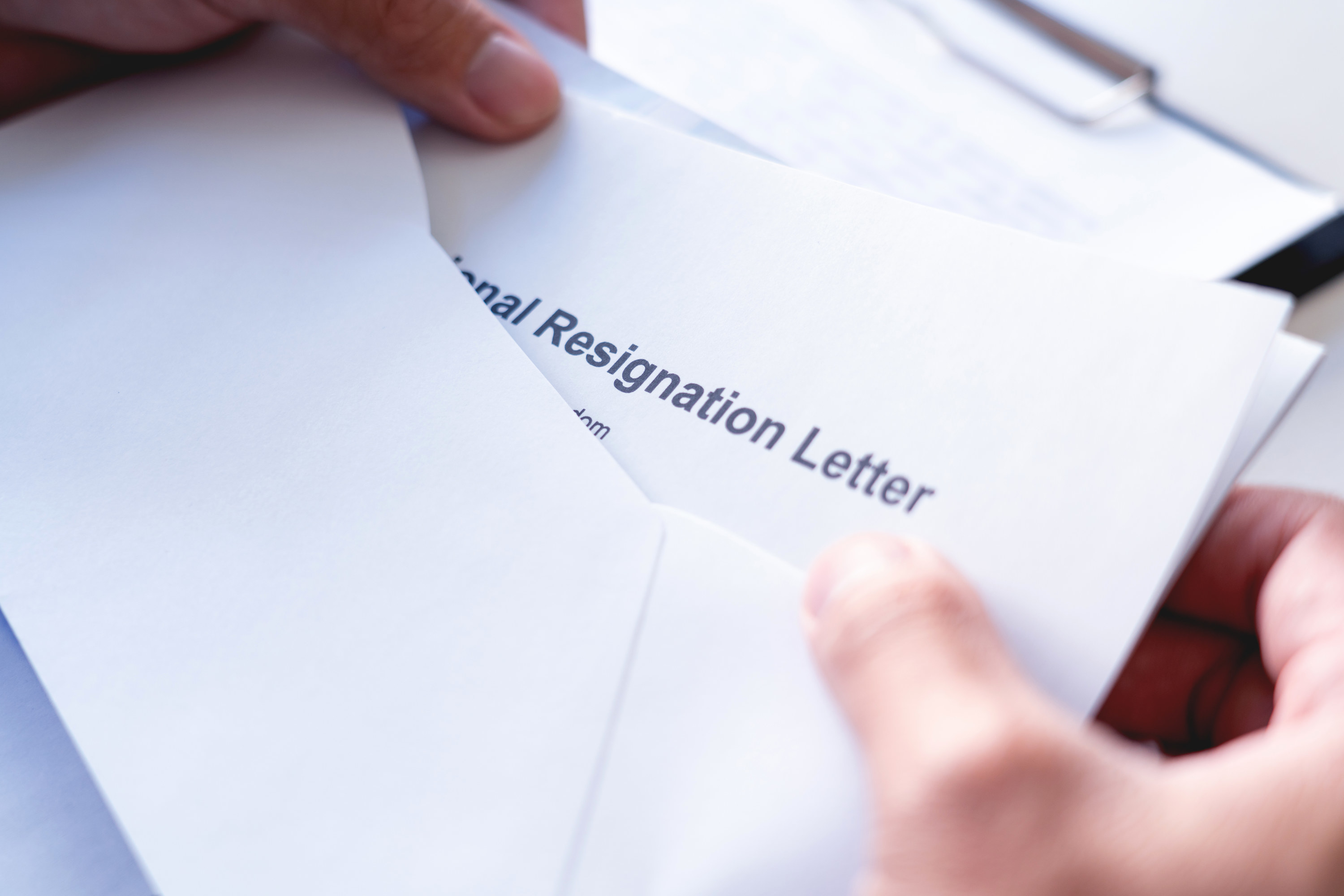 Resignation letter being taken out of an envelope by an employer