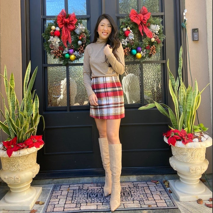 reviewer wearing skirt in red and white with beige top and boots