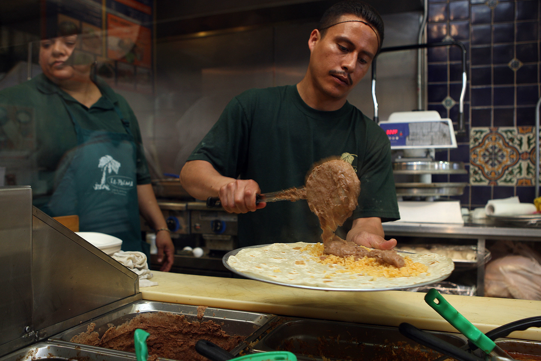 A line cook making a burrito